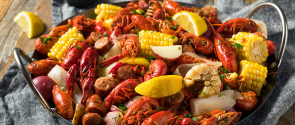 Photo of boiled crawfish with add-ins like corn potatoes corn and onion
